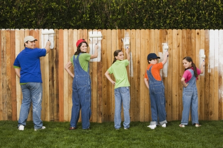 Mixed Race family painting fence