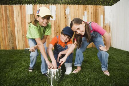 Mixed Race children painting fence Stock Photo - 16095499