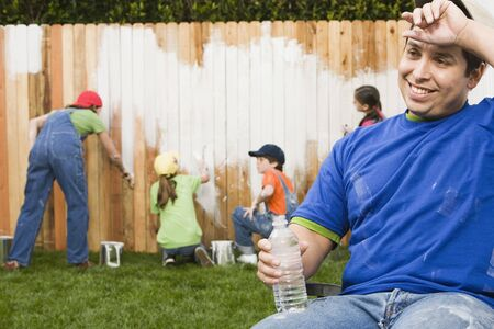 Mixed Race family painting fence Stock Photo - 16095506