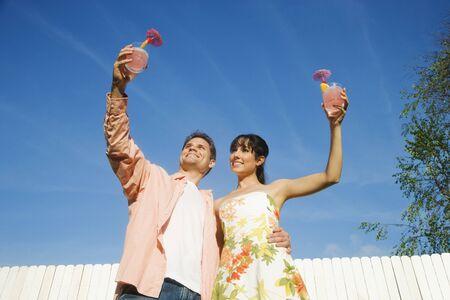 Multi-ethnic couple holding cocktails 版權商用圖片