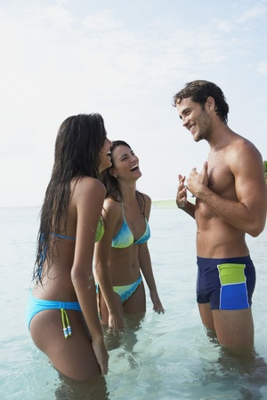Two women talking to man in water Stock Photo - 16095542
