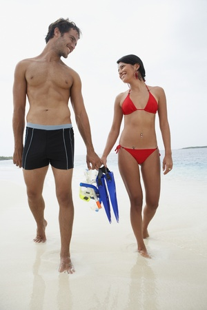 carrying: South American couple carrying snorkeling gear