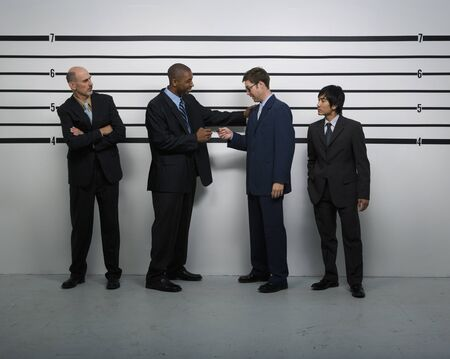 lineup: Multi-ethnic businessmen in police line up LANG_EVOIMAGES