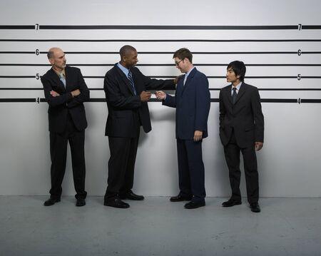 Multi-ethnic businessmen in police line up Imagens