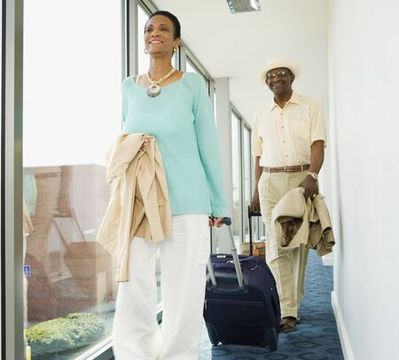 wheeling: Senior African couple wheeling suitcases in hotel LANG_EVOIMAGES
