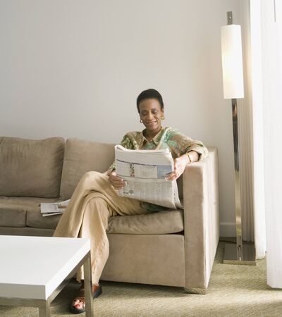 reading a newspaper: Senior African woman reading newspaper LANG_EVOIMAGES