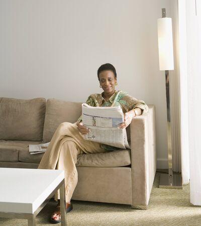 reading newspaper: Senior African woman reading newspaper LANG_EVOIMAGES