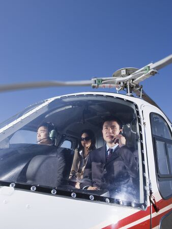 flying man: Asian businesspeople in helicopter LANG_EVOIMAGES
