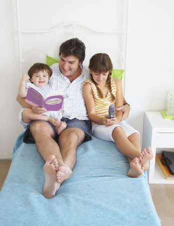 Hispanic father reading to daughters Stock Photo - 16095751