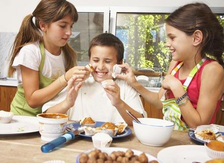 Hispanic siblings decorating cupcakes and being silly Stock Photo - 16095761