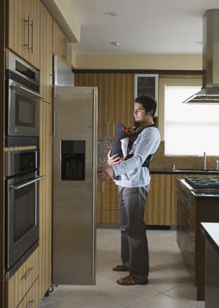 refrigerator with food: Hispanic father and baby looking in refrigerator LANG_EVOIMAGES