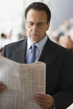 business: Hispanic businessman reading newspaper LANG_EVOIMAGES