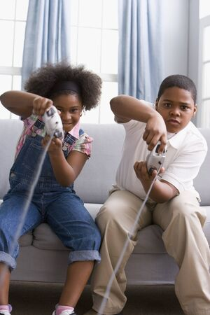 African American sister and brother playing video games Stock Photo