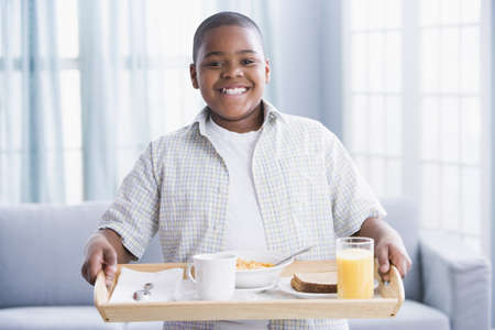 african ethnicity: African American boy carrying breakfast tray
