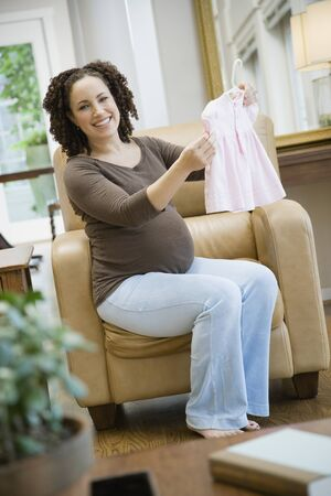 Pregnant African woman holding baby clothes Stock Photo - 16095990