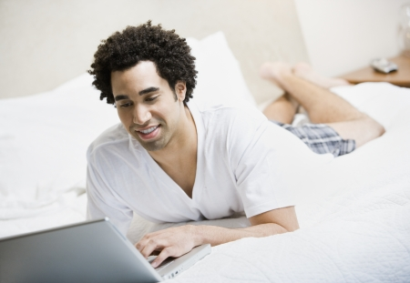 telecommuter: African man typing on laptop