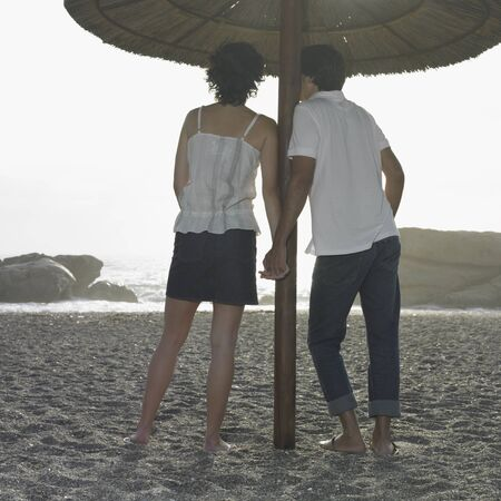 finding a mate: Hispanic couple holding hands on beach