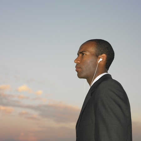 African businessman wearing ear buds Stock Photo