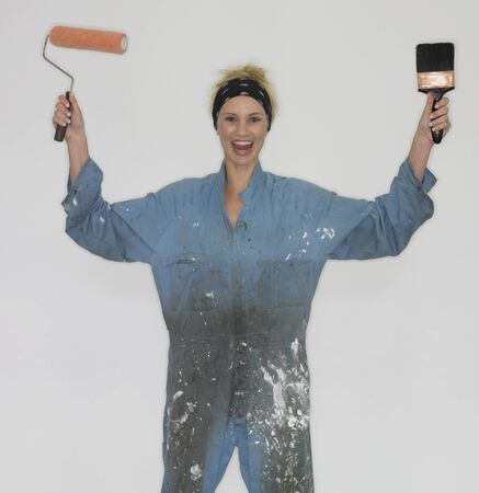 coverall: Woman wearing coveralls and holding paintbrushes