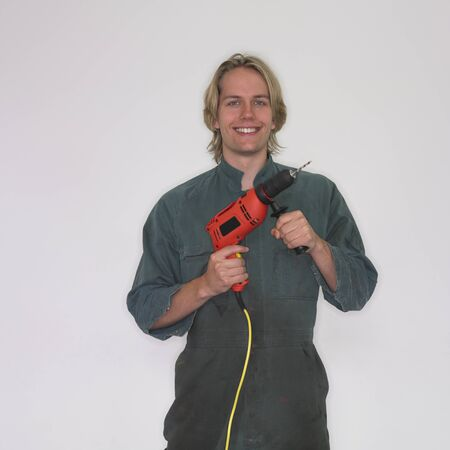 attired: Man wearing coveralls and holding drill LANG_EVOIMAGES