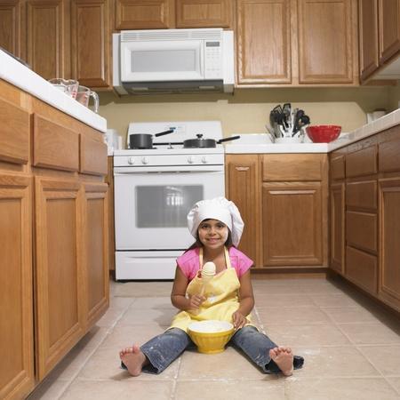 Hispanic girl mixing bowl on kitchen floor Stock Photo - 16096021