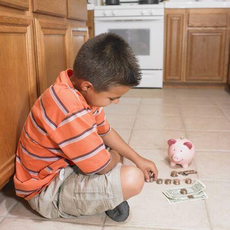 Hispanic boy counting money on floor