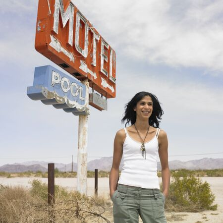 Hispanic woman next to motel sign on beach 版權商用圖片