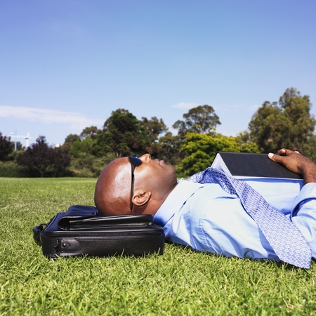 wearying: African businessman laying in grass