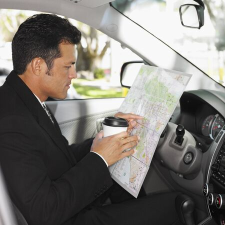 Hispanic man reading map in car Stock Photo - 16096043