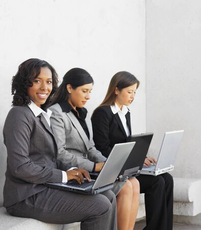 Multi-ethnic businesswoman typing on laptops Stock Photo - 16096047