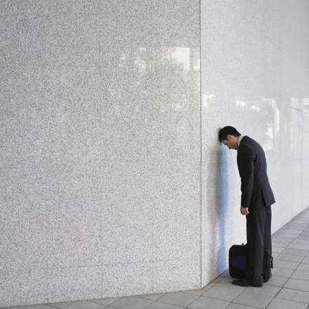 attache: Businessman leaning head on wall