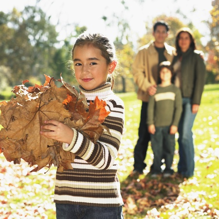 Mixed Race girl playing in autumn leaves Stock Photo - 16096057