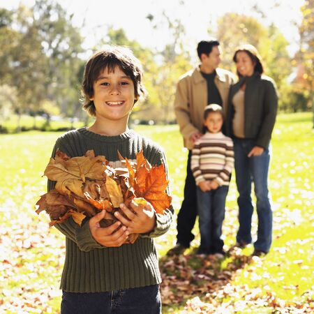 Mixed Race boy playing in autumn leaves Stock Photo - 16096058