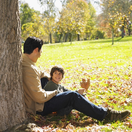 Mixed Race father and son sitting in park Stock Photo - 16096059