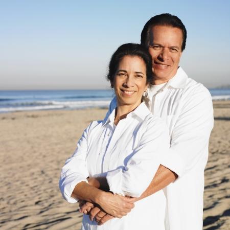 Hispanic couple hugging at beach