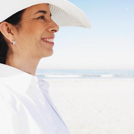 attired: Hispanic woman wearing sunhat at beach