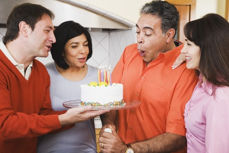 mid adult women: Middle-aged Hispanic man blowing out birthday candles