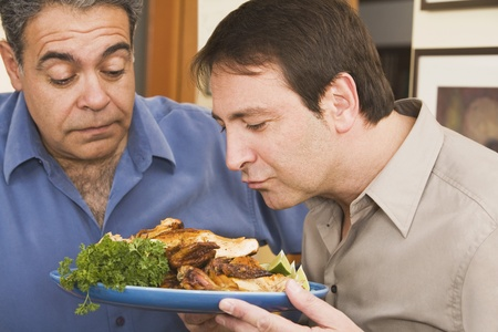 Two men looking at plate of food Imagens