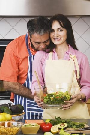 Middle-aged Hispanic couple holding salad