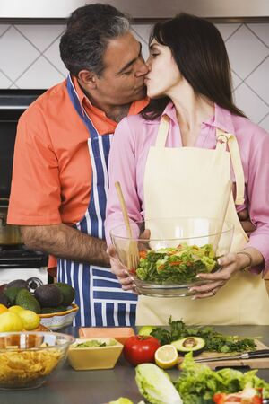 babyboomer: Middle-aged Hispanic couple kissing in kitchen