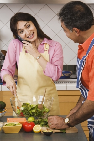 Middle-aged Hispanic couple preparing food in kitchen Stock Photo - 16096085