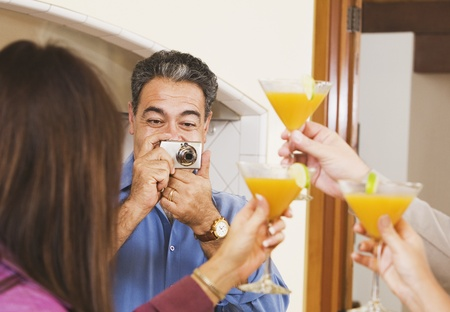 babyboomer: Middle-aged Hispanic man taking photograph of friends LANG_EVOIMAGES