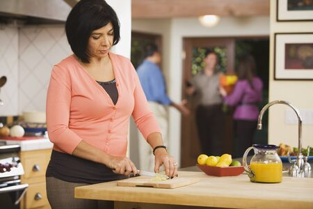 boomers: Middle-aged Hispanic woman chopping lemons LANG_EVOIMAGES