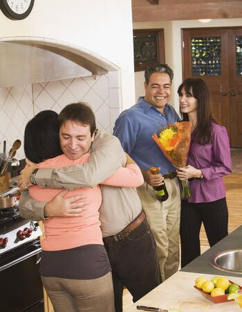 babyboomer: Middle-aged friends hugging in kitchen