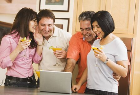 blabbing: Two middle-aged couples looking at laptop