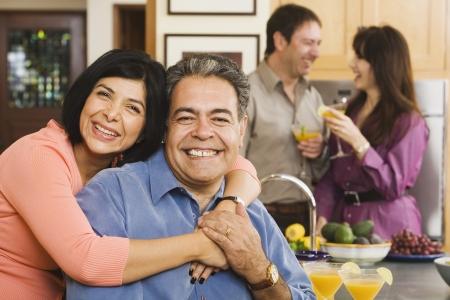 Middelbare leeftijd Latijns-Amerikaans paar knuffelen op het feestje Stockfoto