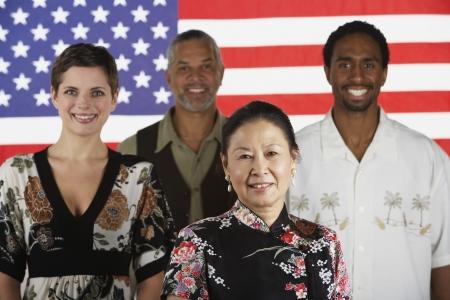Étnico-étnicas personas de pie delante de la bandera americana Foto de archivo