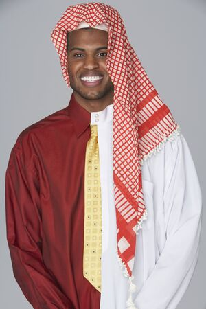 attired: Middle Eastern man wearing traditional dress and business attire
