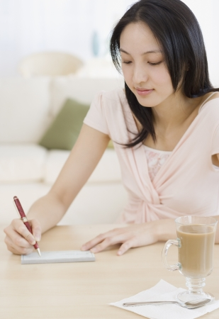 person writing: Asian woman writing letter