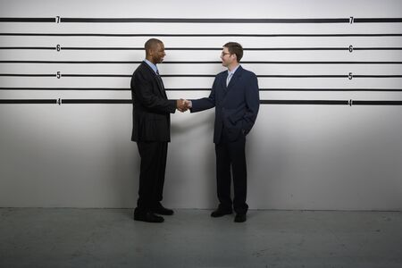 offense: Multi-ethnic businessmen shaking hands in police line up